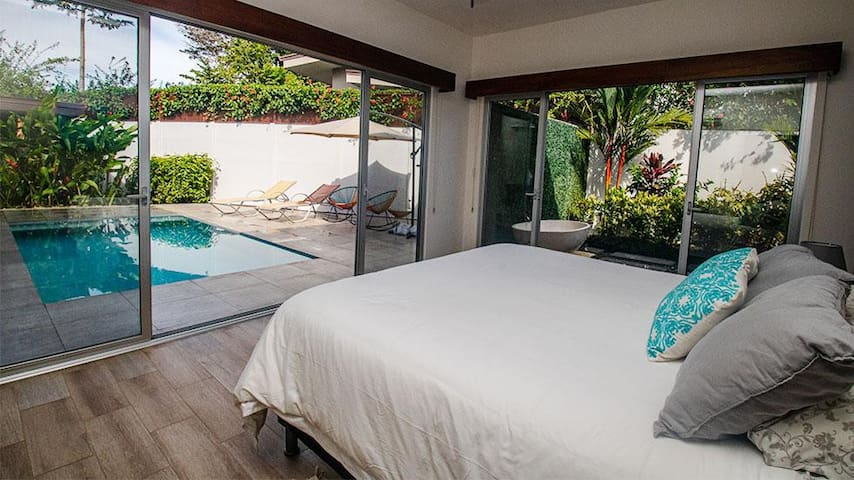 Master bedroom with wide sliders opening to the pool for a midnight dip