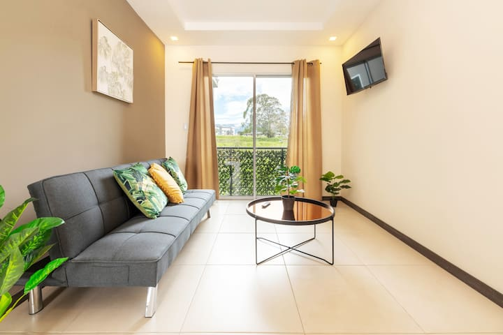 Living room with sliding window and a green view. Smart TV/ Sala con puerta corrediza y vista a lo verde.