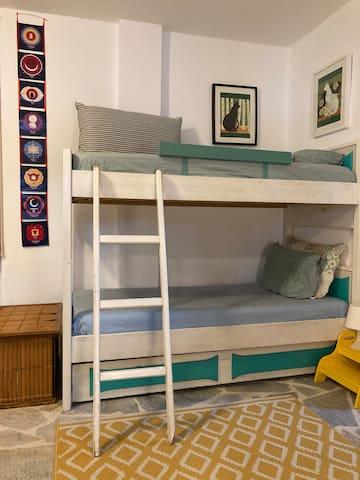 Κουκέτα από μασίφ ξύλο που κοιμούνται τρία άτομα, καθώς από κάτω υπάρχει ειδικός μηχανισμός ανάρτησης για επιπλέον μονό κρεβάτι.