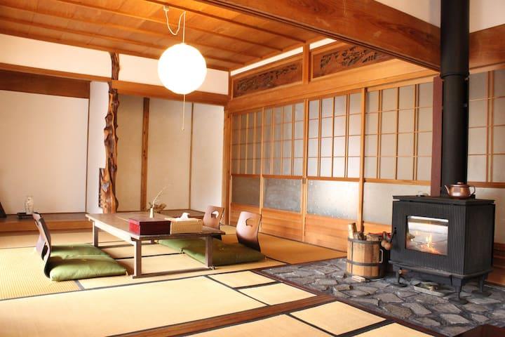 16畳の居間には岐阜県産の薪ストーブがあります。シーズンになると、ゲストの方に薪をくべていただきます。照明は本美濃和紙を使用。岐阜の魅力溢れる設備です。