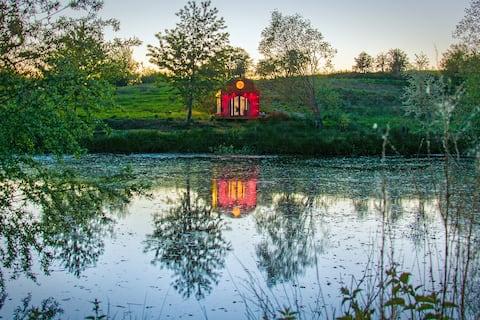 Luxury off-grid waterside glamping pod on a farm