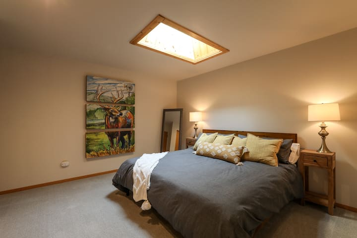 Comfortable king bed with skylight above.  Opposite the bed a closet and dresser.