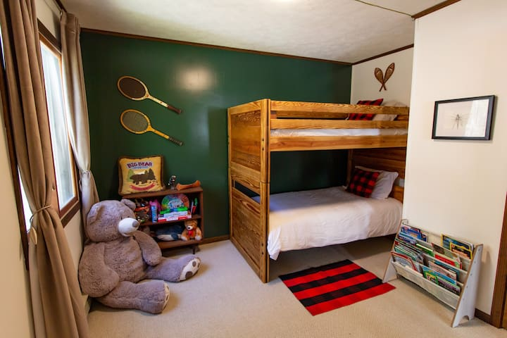 Kids' room with bunk beds, toys and blackout curtains