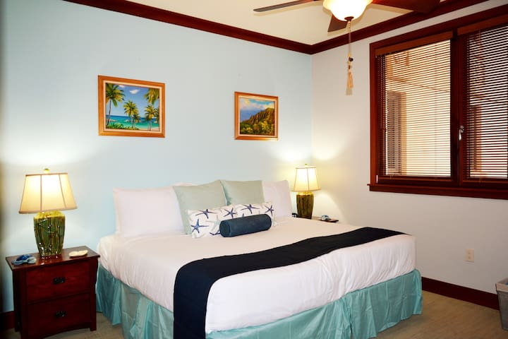 """2nd bedroom with 2 twin beds which can be converted to a King upon request at no charge. It also has a 45"""" flat screen and a full dresser with double closets. Simple color palette and very soothing."""