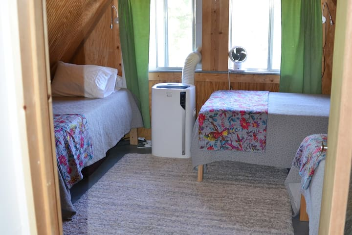 """Bedroom 2: 4 twin beds with new 8"""" Simmons foam mattresses. Room for a toddler bed/foam mattress in the middle of the floor (both a crib mattress and fold up foam mattress are stored underneath the beds).   A/C unit 3 of 3."""