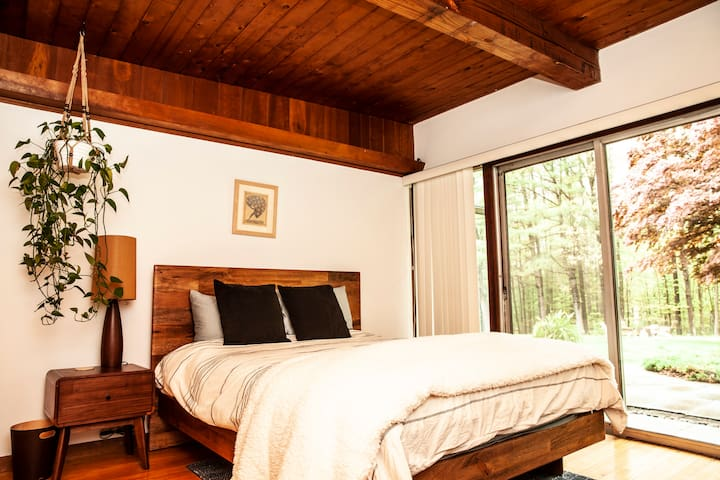 The Zen guest bedroom features a beautiful reclaimed wood bed, brand new queen mattress, solid oak nightstand, a sitting area, and a sliding door to the yard.