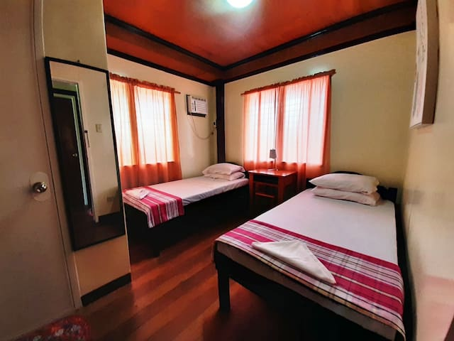 Room 2.  Two  single beds with working table and dedicated toilet/bath.
