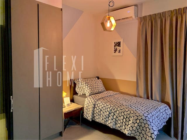 Guest Bedroom Downstairs with Cozy Single Size Bed, Comfy Big Pillows and Table Lamp by the Bed