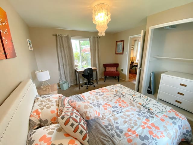 The spacious bedroom with queen bed, dresser and desk.