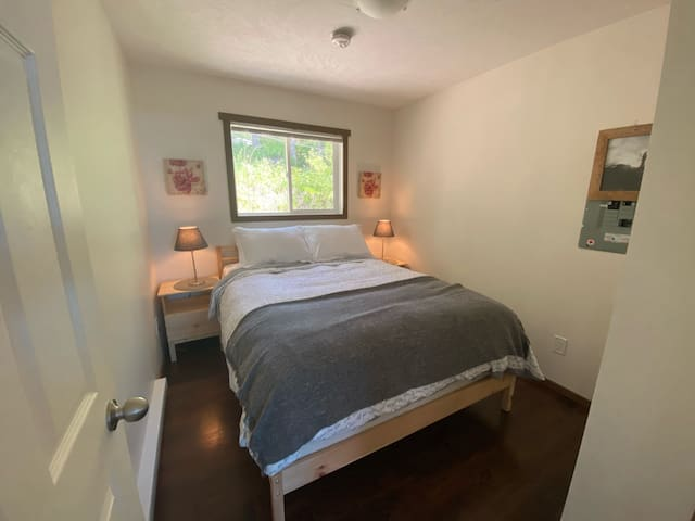Cabin 2: Bedroom with queen bed and wardrobe with extra bedding and beach towels