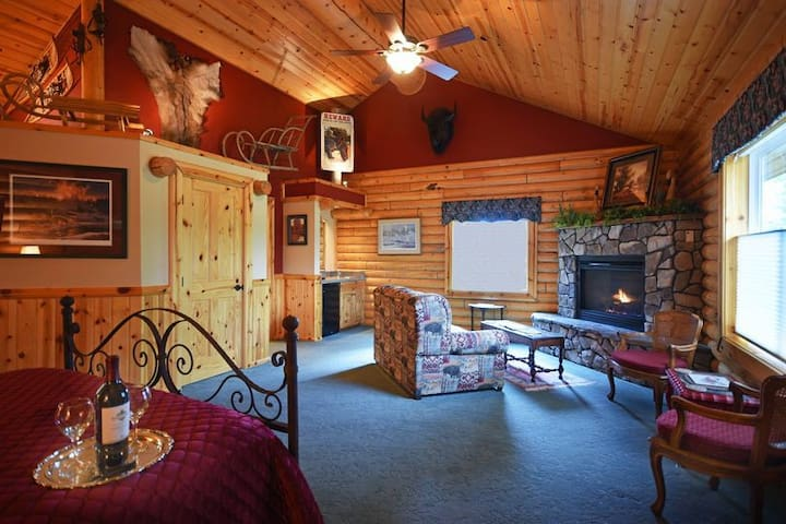 """Yellowstone Suite:  Queen Bed, Jacuzzi Tub in Private Bathroom, 50"""" Screen TV,  Keurig Coffeemaker, Gas Fireplace, Outside patio with Bistro Table."""
