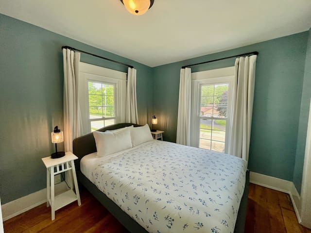 Bedroom with queen bed, dresser, closet, and blackout curtains