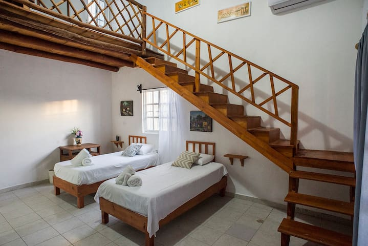Two single beds in spacious loft room.