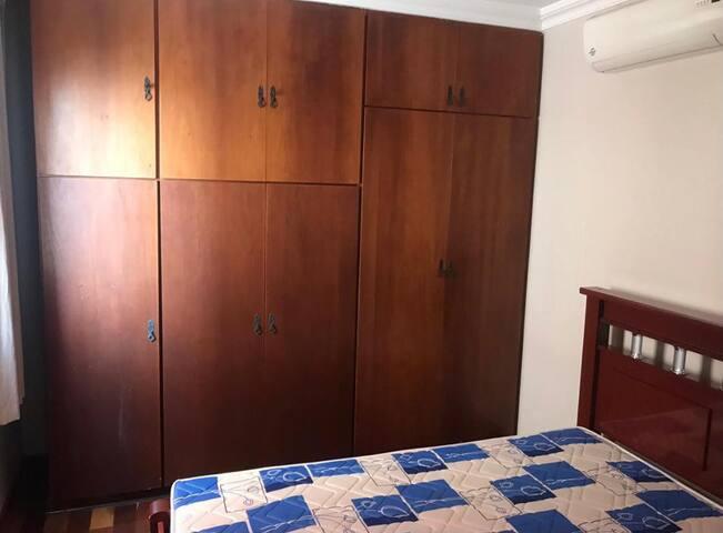 Quarto master com dois armários planejados e ar-condicionado.