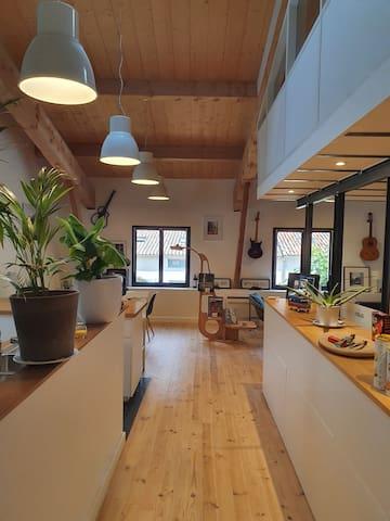 En rentrant, la cuisine à gauche, la salle à manger et le coin salon au fond