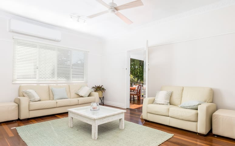 Spacious living room flowing out to deck with leather couches, air-conditioning and smart TV.