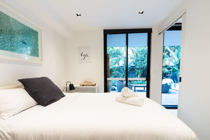 Come evening, retreat to a immaculate bedroom that's furnished with a queen bed, floor-to-ceiling windows that overlook the courtyard, built-in wardrobes and modern artwork.