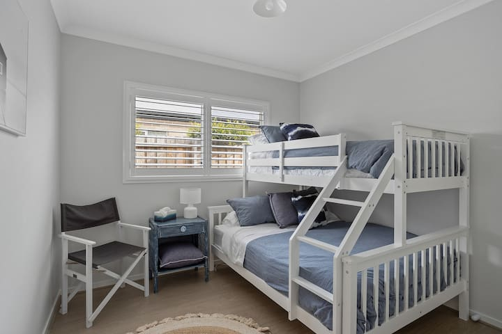 clean and comfortable bedroom with tri bunk bed