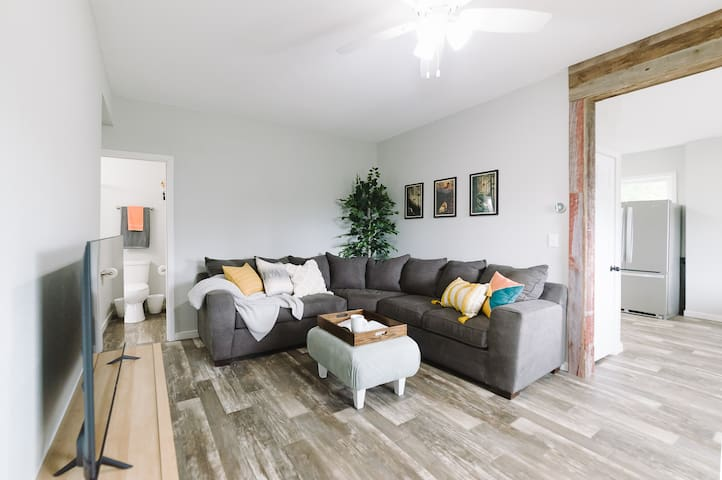 """The living room features a plush, oversized couch, and a 55"""" smart TV; perfect for resting and relaxing."""