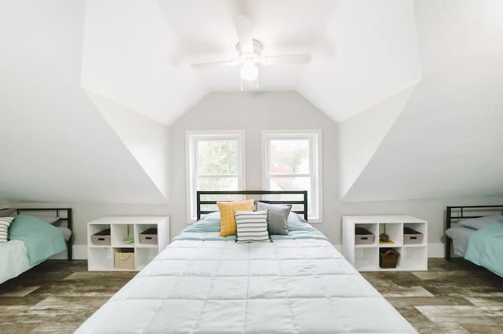 On the other side, you'll find the bunk room! This wide-open bedroom has one queen bed in the middle and one twin daybed tucked under the sloped ceiling in corner end of the room.