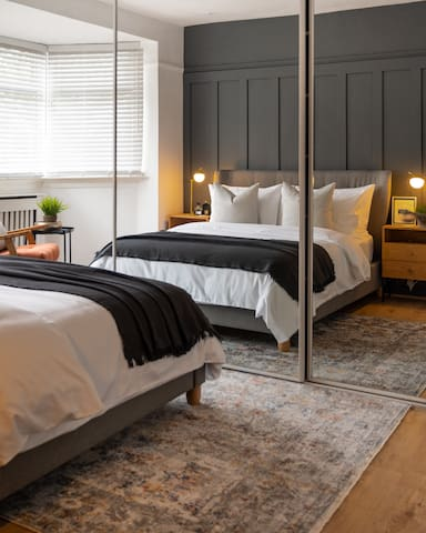 Double bedroom with floor to ceiling fitted mirrored wardrobes. The dark wall makes this room dramatic and cosy. Curl up with a book in the inviting armchair positioned perfectly in the window.