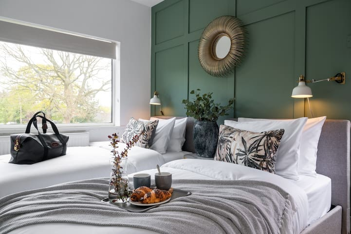 Twin bedroom with stylish bedding and an on trend green feature wall that evokes a feeling of calm and tranquility.