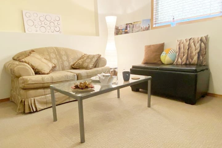 Comfy couch, cute side bench and tea table with tea amenities.