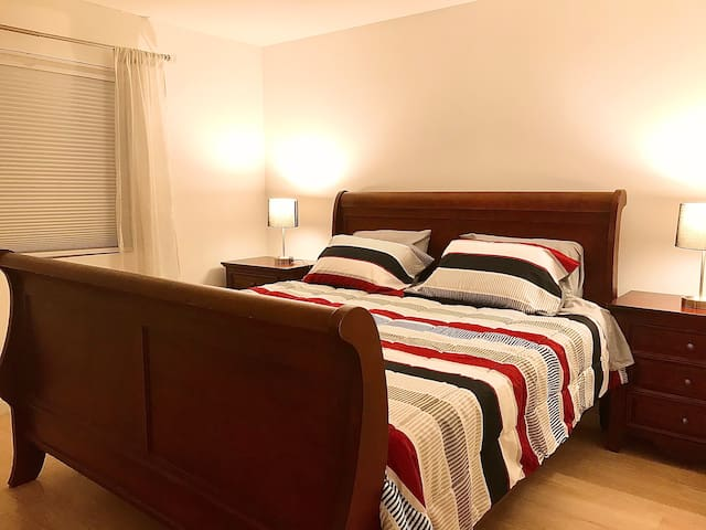 King size bed in bedroom with room darkening shades.
