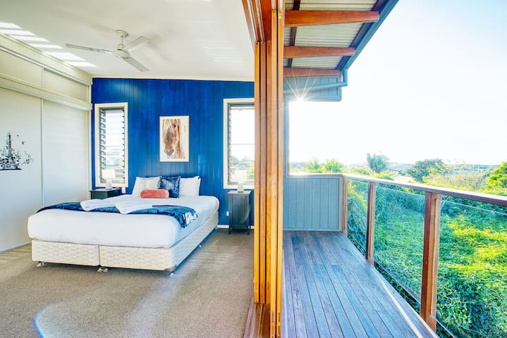 The master bedroom features bi-fold doors to a private balcony, capturing breathtaking views directly from bed.