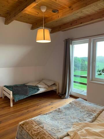 Duża sypialnia z balkonem. Jedno łózko podwójne i jedno pojedyncze.