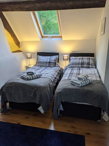 This bedroom has two single beds and a futon.  The two single beds can be joined together as one kingsized bed if preferred. It has it's own en suite shower, sink and toilet. Lovely view to the north from the bedroom and the en suite.