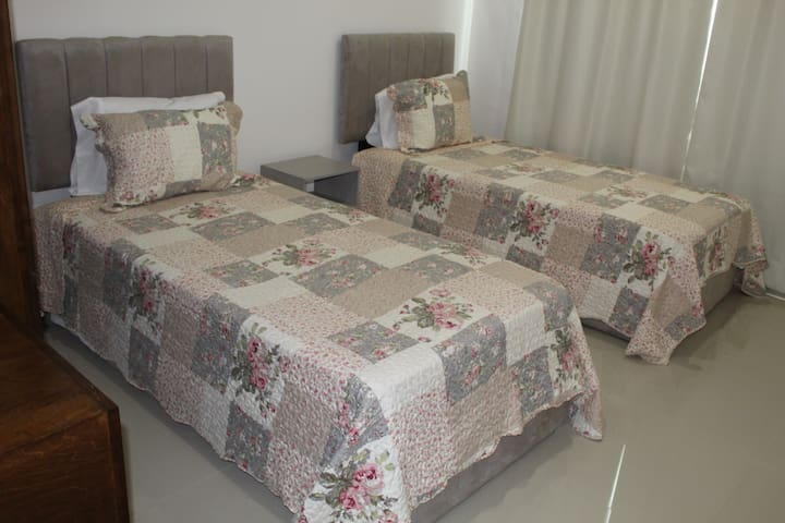 Recámara con dos camas individuales, closet y un pequeño escritorio.