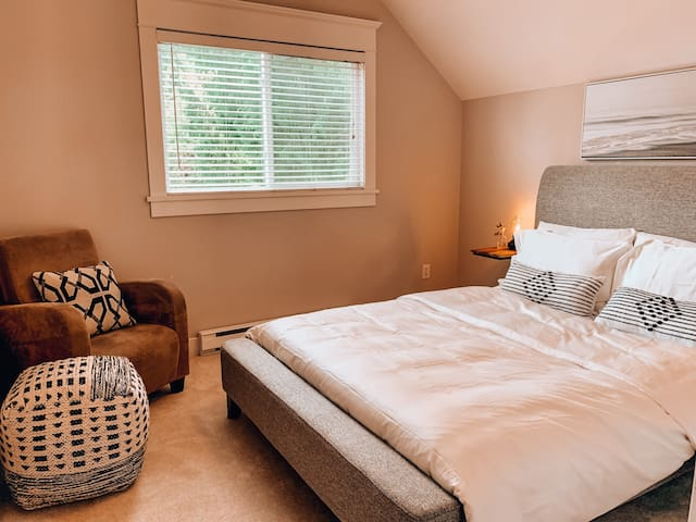 The bedroom features a Queen size bed complete with an upholstered bed frame and luxurious 400 thread count linens. The reading nook allows perfect space for working or curling up with a good book.