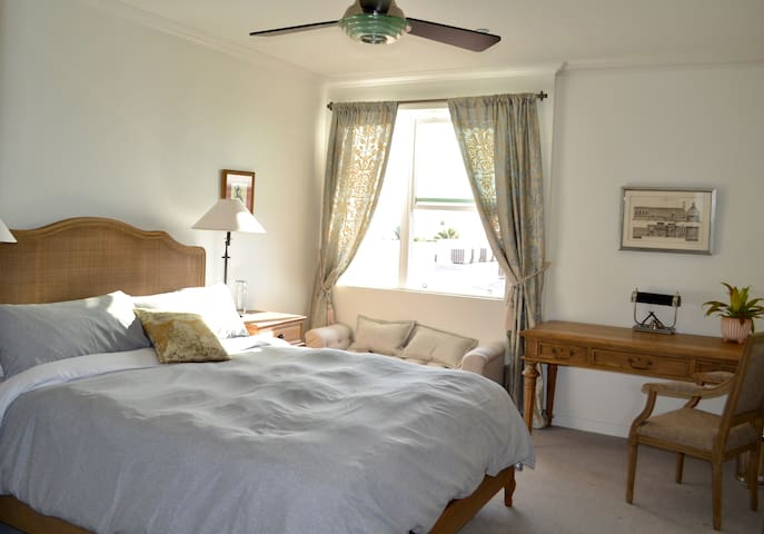 King Size bed, window seating,  and large desk.