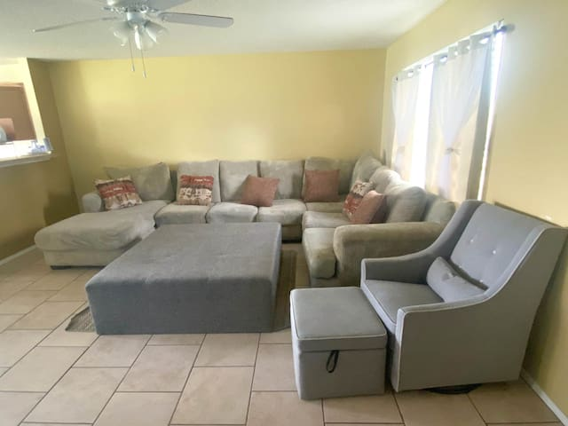 Spacious living room with a comfortable sofa and rocking chair with ottoman. Large center ottoman as well