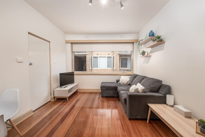 Lounge room with comfy couch and Smart TV for you to relax in with large windows and plenty of natural light