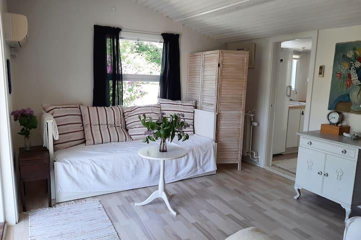 Fra verandaen kommer man ind i den lille stue, hvor sofaen kan trækkes ud til dobbeltseng  From the veranda you enter into the livingroom, where the couch can be turned into double sleeping facilities