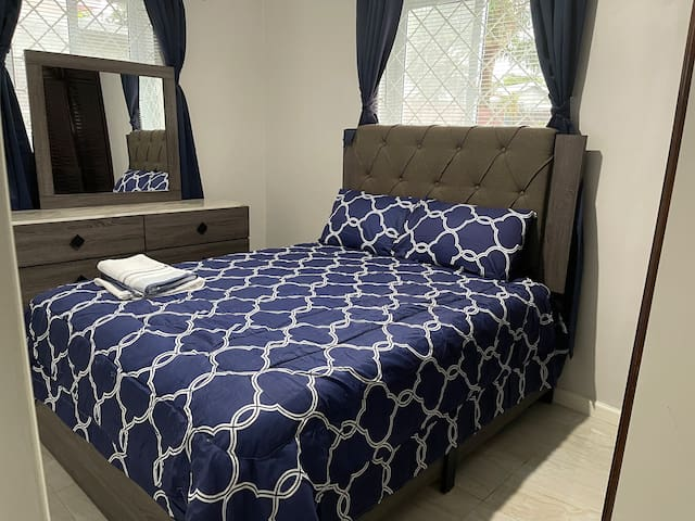 The second bedroom with queen bed and dresser.