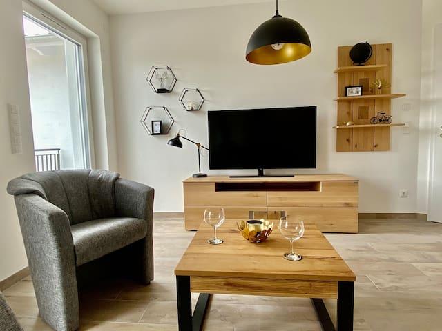 Wohnzimmer mit Fernseher und Balkonzugang