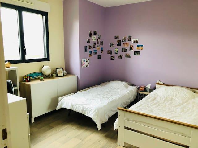 Chambre enfant aux couleurs douces, avec literie confortable, et bureau Bedroom with 2 singe beds , with sweet colors, confortable beds and a desk