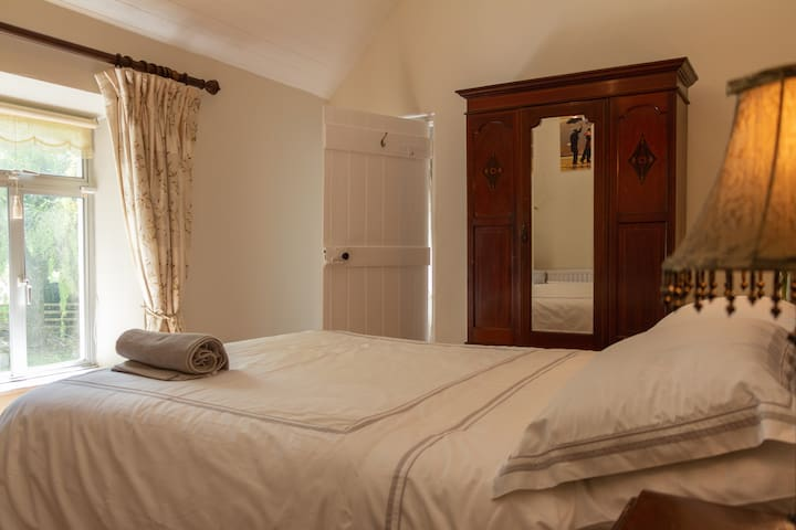 Elegant main upstairs bedroom  with original boarded high ceiling,boarded door and wooden floor.All the upstairs bedrooms have similar features.