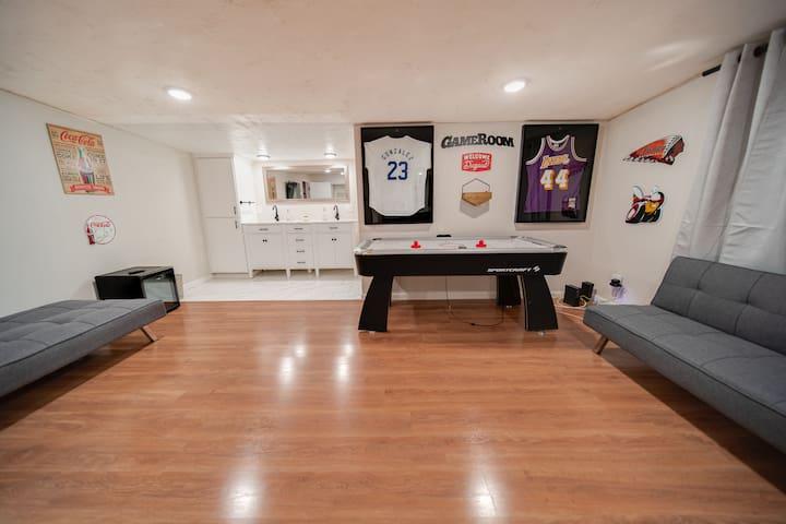 Bonus room with air hockey table, TV, 2 sofa matresses, small beverage fridge, full bathroom, and double vanity.