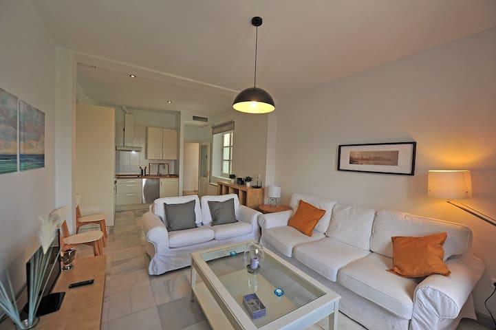 Espacioso salón-comedor con sofa-cama, TV y mesa de comedor entre otros. Al fondo la zona de cocina.