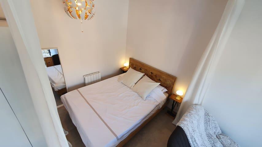 L'espace nuit ouvert : un lit 160/200 en manguier massif, table de chevet de créateur. Sur la gauche, on distingue la penderie.