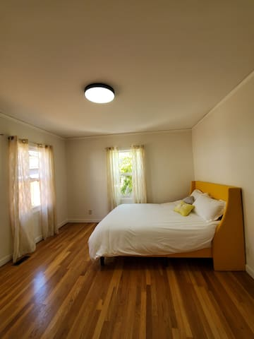 Spacious bedroom with queen sized bed and windows.