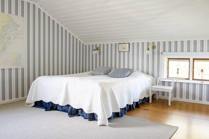"""Dubbelsängen i det största sovrummet """"Rådmansö"""". Rymligt med plats för extrasäng och/eller spjälsäng. Fönster åt två håll."""