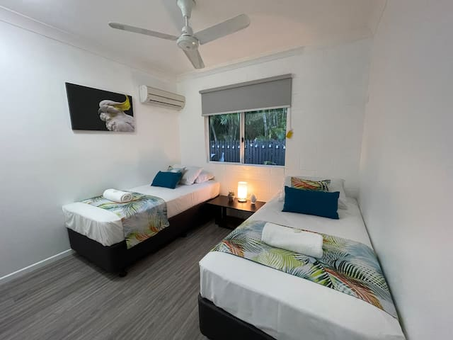 Bedroom 3. Perfect for kids or adults.  2 single beds, air conditioning, ceiling fan, built in robe, luggage rack and the window looking out over the patio area.