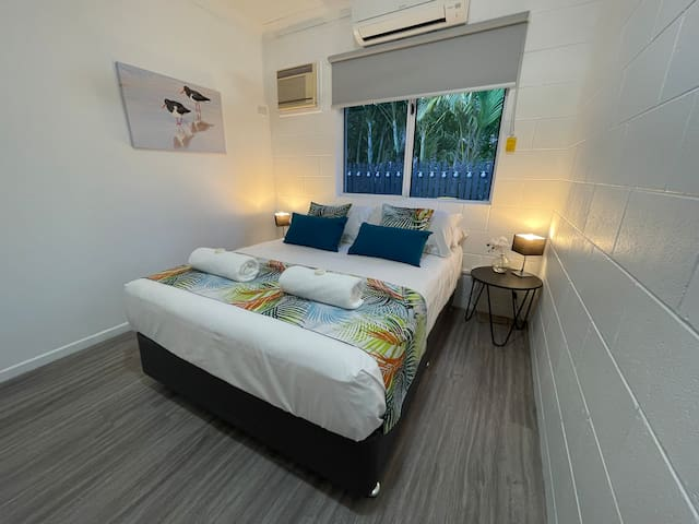 Bedroom 2. With inviting double bed, air conditioning, ceiling fan, built in robe, and views to the back patio. We love the gorgeous splash of colour with our custom made bed runners and cushions. Storage galore with built in robe and luggage rack.