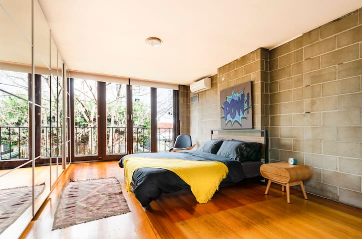 main bedroom queen size bed and balcony overlooking back yard and tall tree