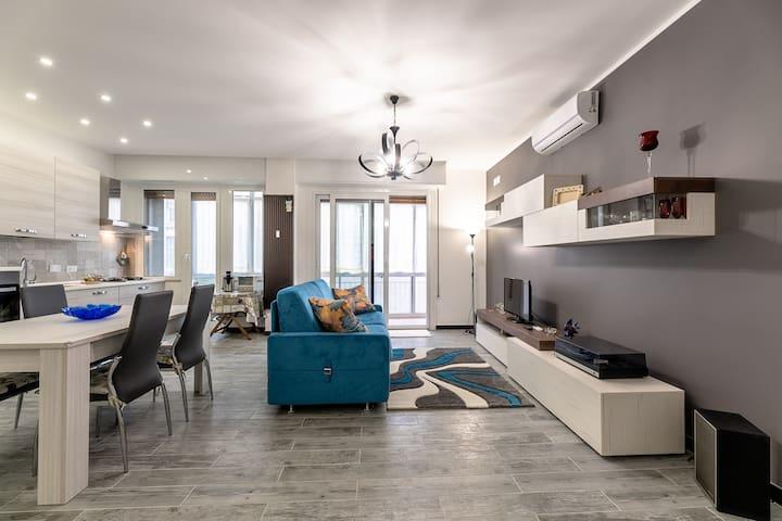 due ambienti in uno: living con divano e tv, e cucina attrezzata con tavolo da pranzo